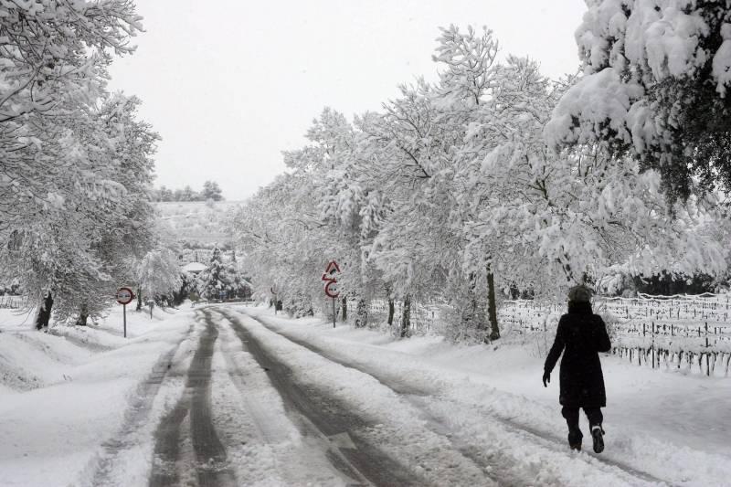 Una mujer camina por una carretera nevada en las inmediaciones de l'Espluga de Francoli (Tarragona), uno de los pueblos catalanes afectados por el temporal de nieve. / EFE