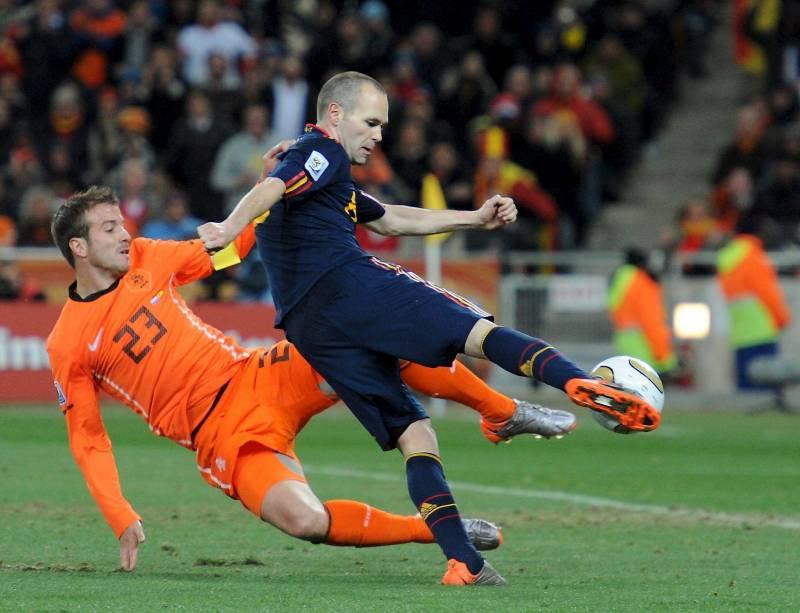 Iniesta golpea el balón ante Van der Vaart. / EFE
