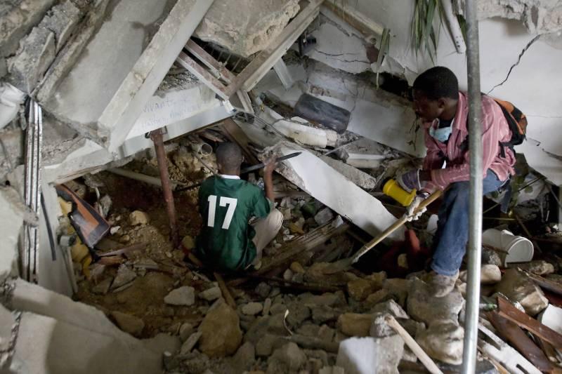Dos haitianos tratan de despejar los escombros en un intento de rescatar a los supervivientes en el Hotel Montana de Puerto Príncipe.