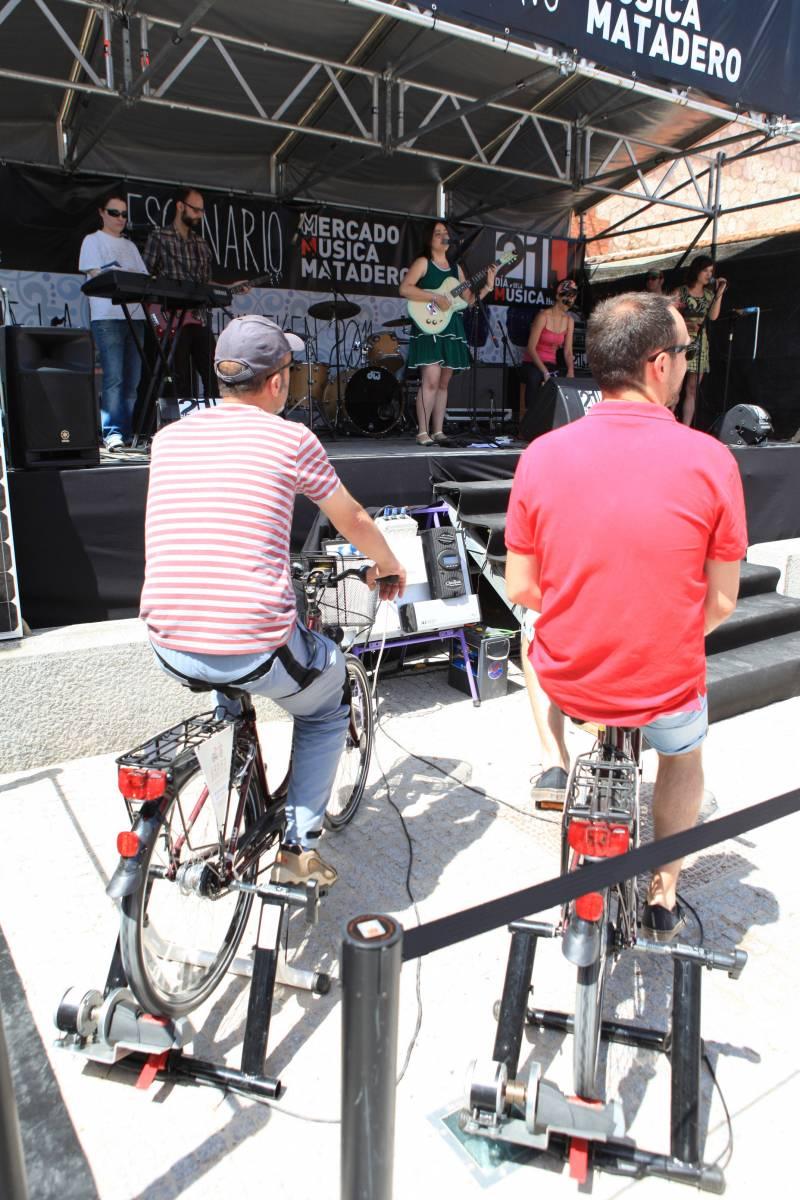 Dos asistentes del festival pedaleando en bici estática delante de un escenario