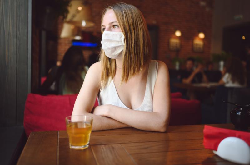 mujer con mascarilla dentro de un bar
