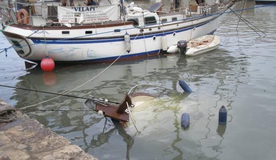 Embarcación hundida por una rissaga que sufrió el puerto de Ciutadella / Joan Martinez