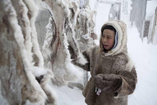 Niño inuit limpiando pieles para confeccionar ropa (Canadá) / EFE