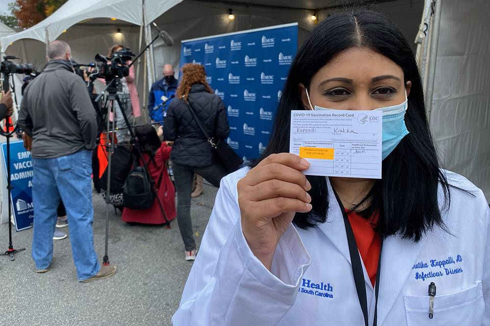 Krutika Kuppalli, una de las médicas que han sufrido amenazas en la pandemia, muestra su tarjeta de vacunación