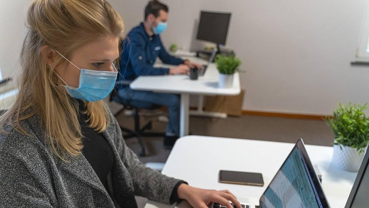 personas trabajando con distancia y mascarilla