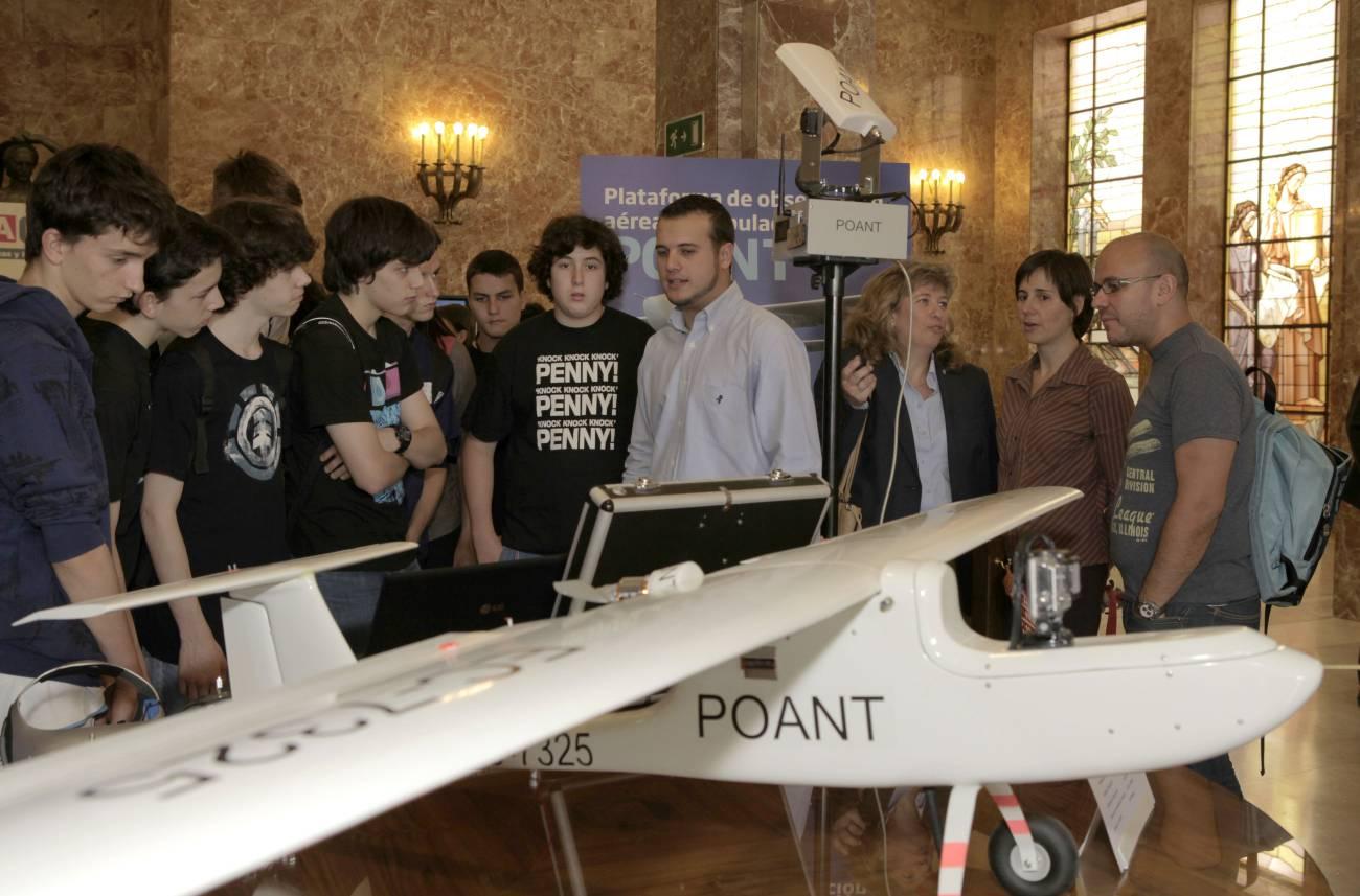 Enrique plaza (con camisa en el centro), explica a un grupo de estudiantes las características de su prototipo