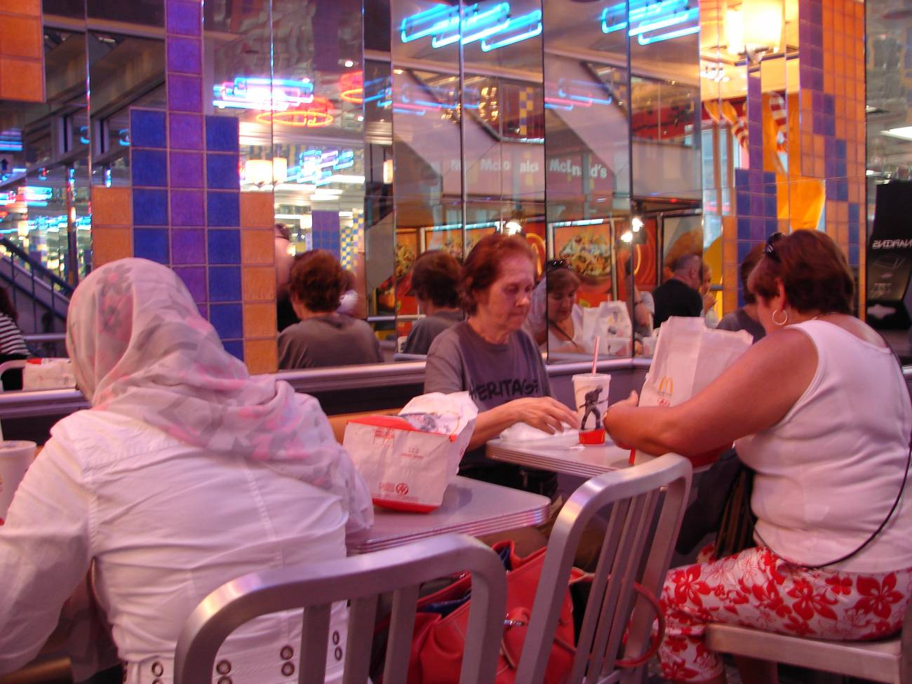 Tres mujeres comen hamburguesas en un restaurante de comida rápida.