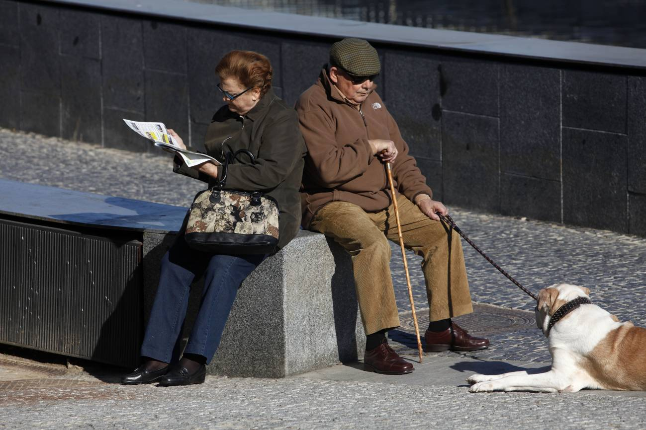 Dos personas toama el sol en una plaza.