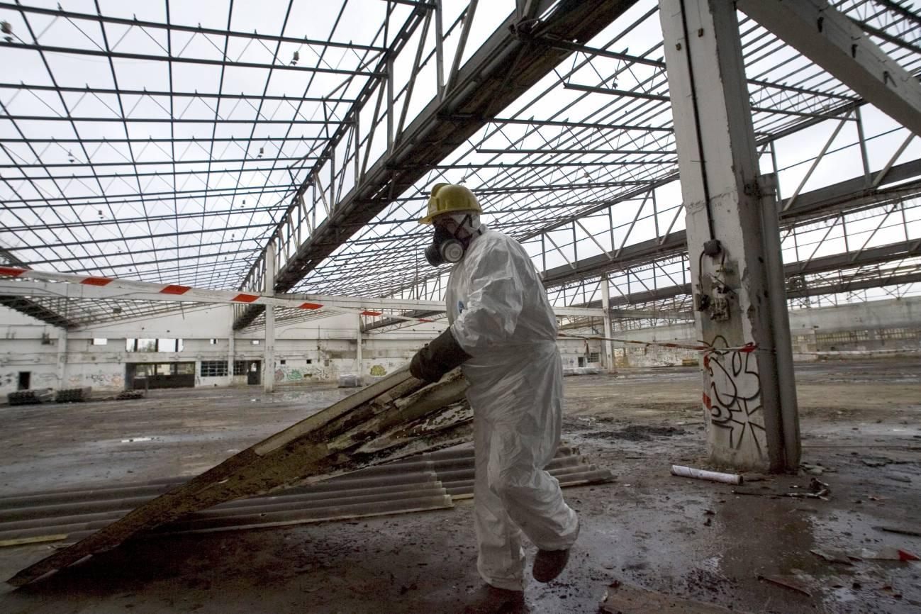 Un operario retira ruinas industriales contaminadas de amianto en el País Vasco. / Efe