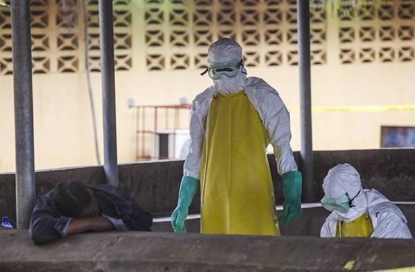 Trabajadores de salud liberianos se preparan para recoger el cuerpo de una víctima del ébola del área de espera de un hospital en Monrovia. / Efe