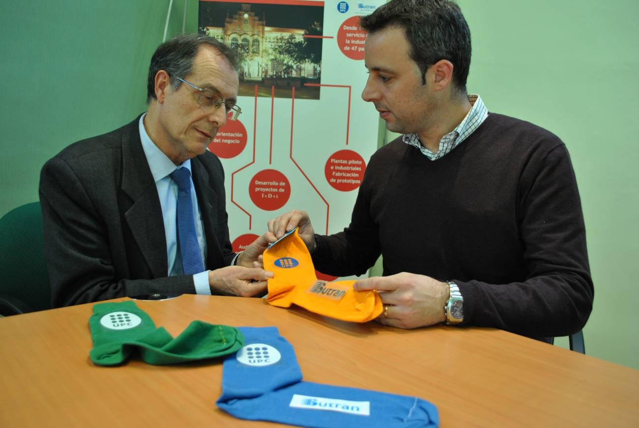 Feliu Marsal, del Centro de Innovación Tecnológica y Óscar Delmau, de Sutran I+D, muestran los nuevos calcetines. Imagen: UPC.