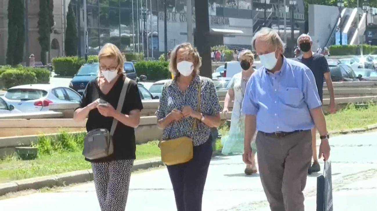 Personas paseando con mascarillas en exterior
