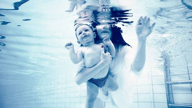 madre con su hijo en una piscina