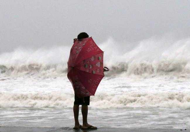 Una mujer se protege del viento del tifón Hagupit en Borongan (Filipinas). / Efe