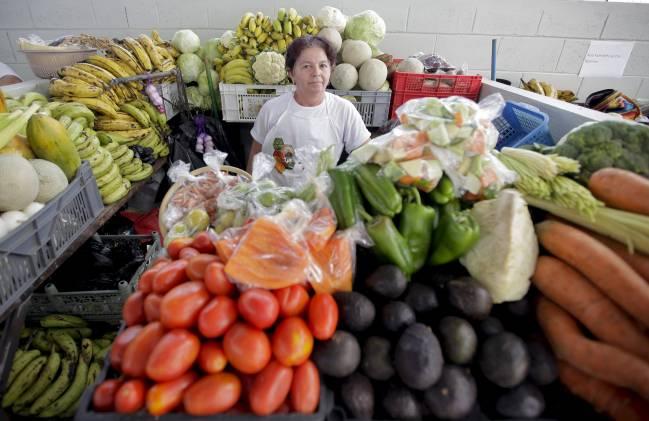 Una mujer compra frutas y verduras el 6 de septiembre de 2014, en un mercado de San Salvador. / Efe