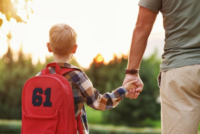 niño con mochila de espaldas y con su padre de la mano