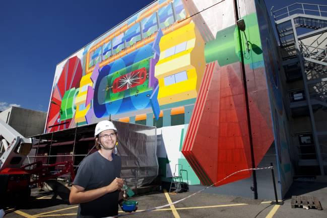 El artista estadounidense Josef Kristofoletti, ante el mural del ATLAS en el CERN