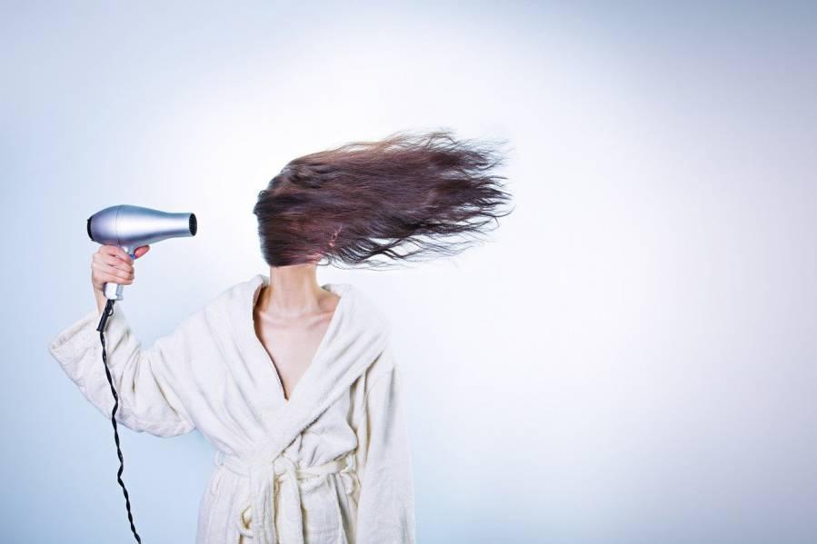 mujer secándose el pelo con mucha intensidad