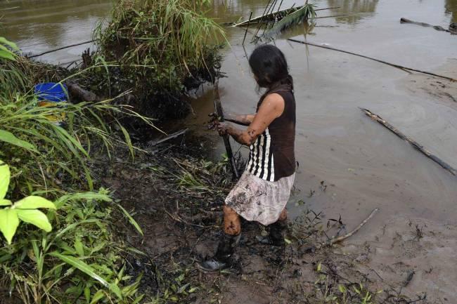 Pobladores limpian un derrame de petróleo este martes, 9 de febrero de 2016, en el municipio de Chiriaco, en la región de Amazonas (Perú). / Efe