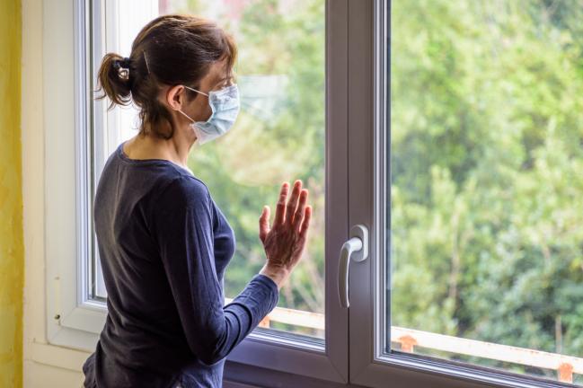 mujer con mascarilla mirando por la ventana