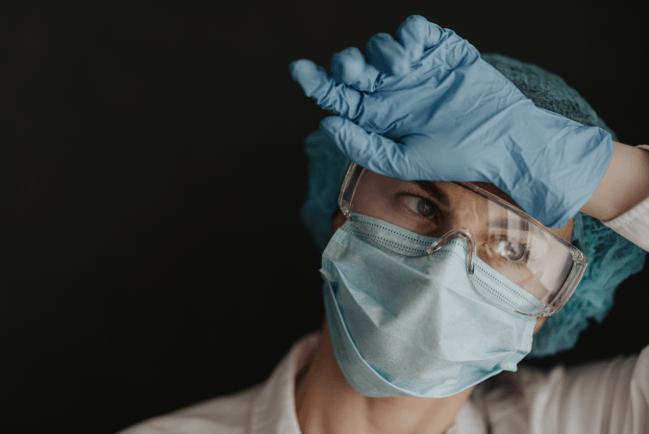 sanitaria con mascarilla y gesto cansado