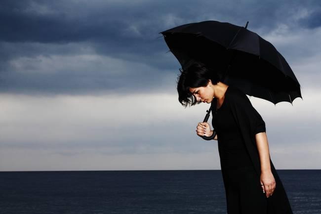 mujer de negro con un paraguas