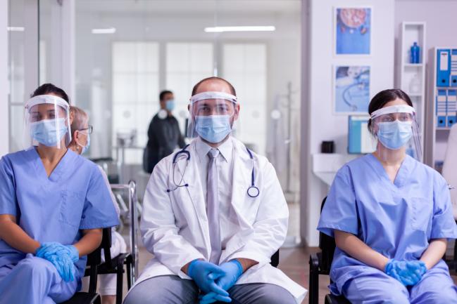 dos enfermeras y un médico sentados y con el equipo de protección