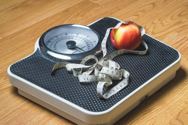 báscula con un metro y una manzana encima