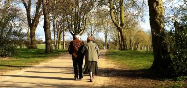 Dos personas mayores caminan por un espacio natural