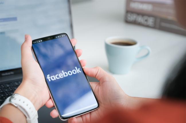 persona con la aplicación de Facebook abierta en el móvil