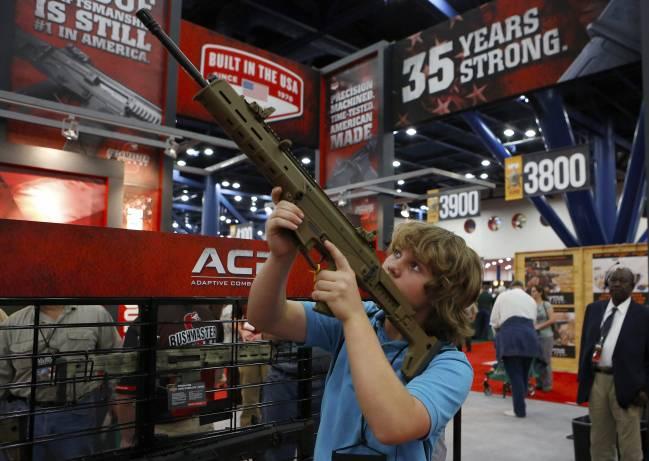 Un niño de 13 años prueba un arma en la convención anual de la Asociación Nacional del Rifle en Houston (EE UU)./ Efe