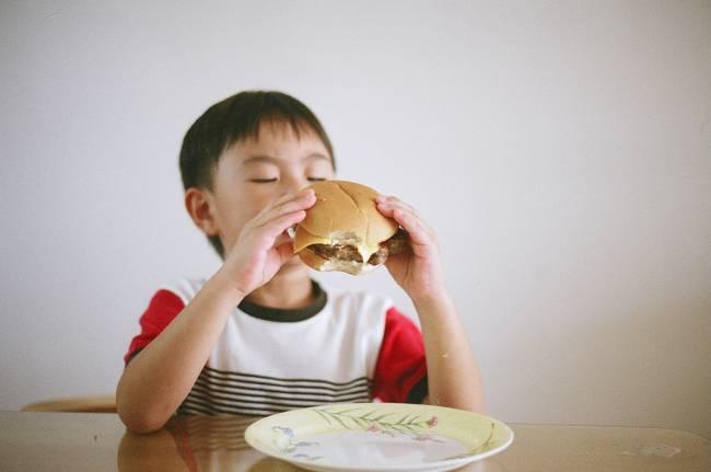 Niño comiendo una hamburguesa, alimento típico en la dieta americana