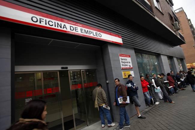 Gente haciendo cola frente a una oficina de empleo