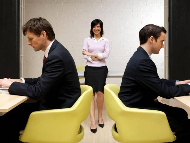 Oficina con dos hombres al ordenador y una mujer de pie en el centro