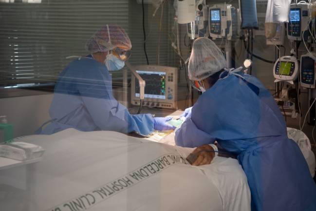 Dos sanitarios atienden a un paciente hospitalizado de covid-19