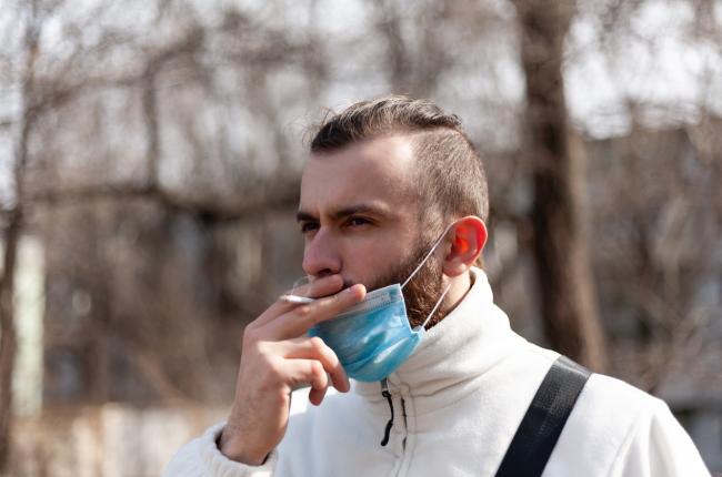 hombre fumando en la calle con mascarilla