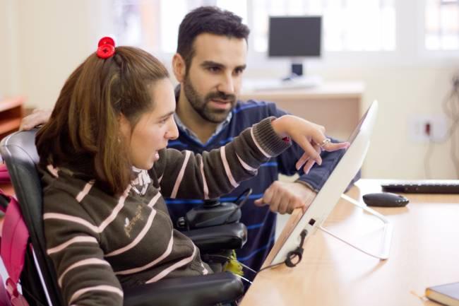 David Valenzuela, trabajador social de ASPACE, enseña a Cristina a usar el videojuego desarrollado por investigadores de la Universidad de Sevilla
