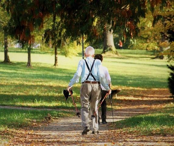 Fotografía de dos personas de avanzada edad paseando por un parque.