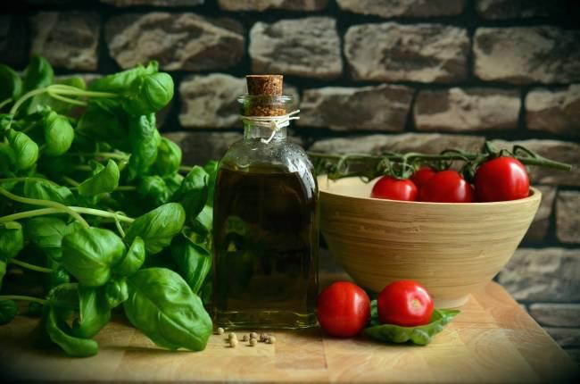 Productos típicos de la dieta mediterránea sobre una mesa de madera: una botella de aceite, un cuenco con tomates y hojas de albahaca