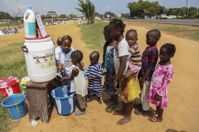 Niños se lavan las manos en una aldea de Liberia. / Efe