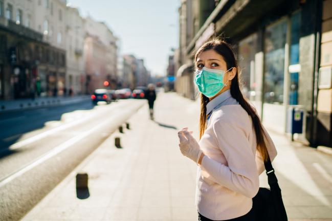 mujer con mascarilla en la calle mira hacia atrás con ansiedad