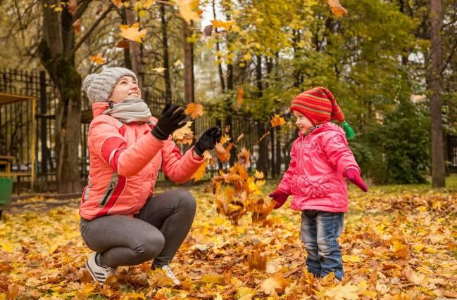 Fotografía otoñal de una mujer y un niño, jugando con las hojas caídas de  los árboles, en un parque.
