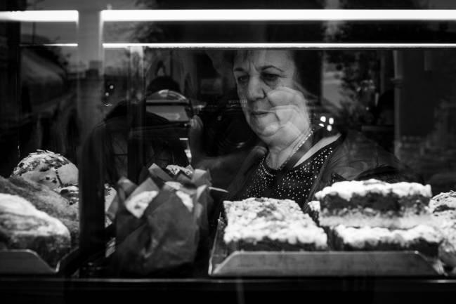 Mujer mayor mirando una vitrina con pasteles. Imagen: Pxhere.com