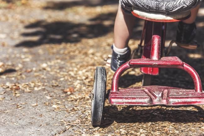 niño en un triciclo