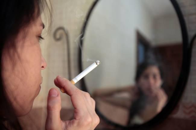 Chica fumando un cigarrillo delante de un espejo