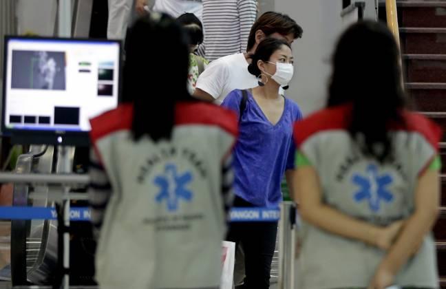Miembros de un equipo sanitario observan la temperatura corporal de los viajeros en el aeropuerto de Rangún (Birmania). EFE / Archivo
