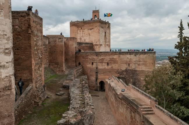 Vista en primer plano de la barbacana y muralla de la Alcazaba, por detrás la torre de armas y al fondo torre de la Vela