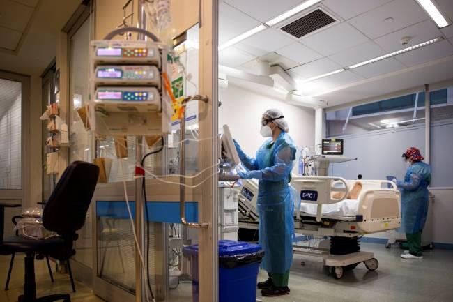 Enfermeras atienden a un paciente covid-19 en una habitación de hospital