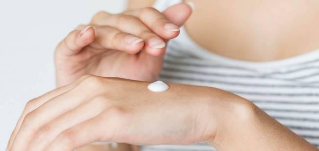 mujer echando crema en sus manos