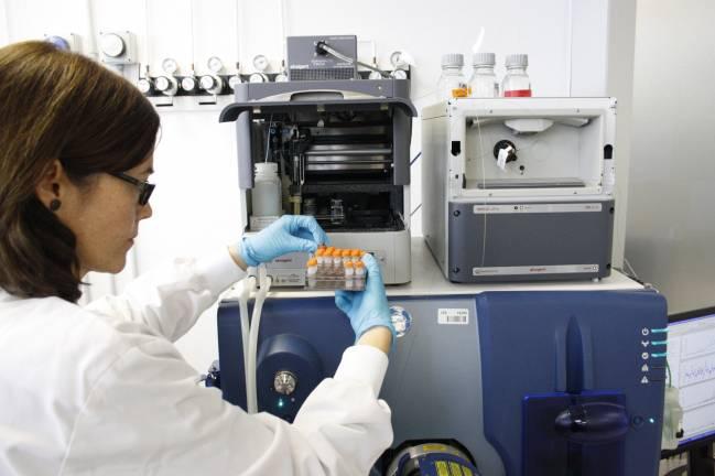 La Dra. Eva Borrás, de la Unidad de Proteómica del CRG y la UPF, introduciendo unas muestras de líquido cefalorraquídeo en el espectrómetro de masas.